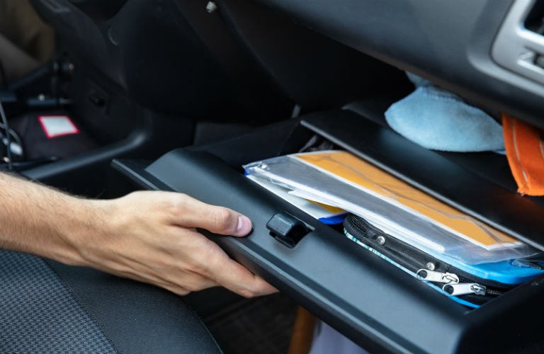 Hand holding open vehicle glove box with paperwork inside